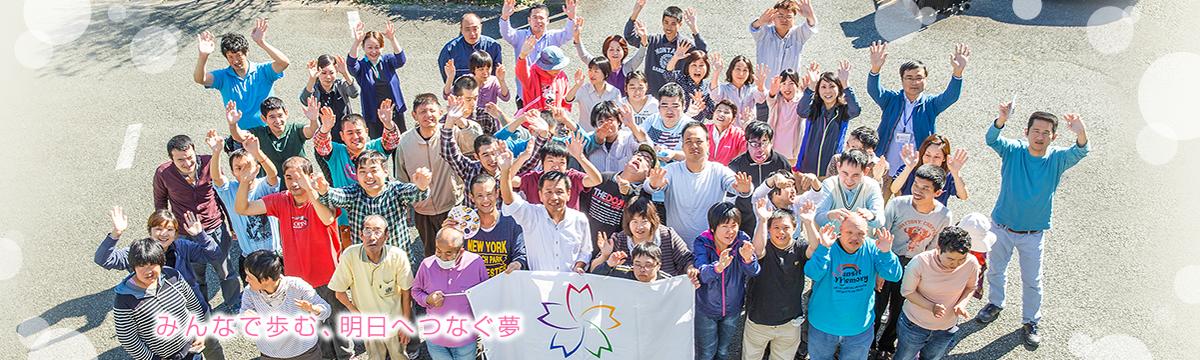 社会福祉法人 桜木会の利用者、スタッフのみんなの集合写真です。みんなで歩む、明日へつなぐ夢。